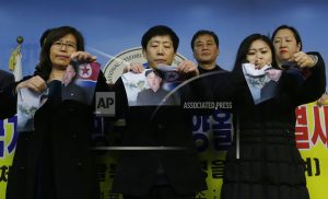 Activists rip Kim Jong Un's photo in Olympic protest