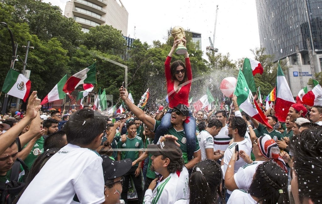 Mexico City – Mexican soccer fans and pride marchers mingle in celebration